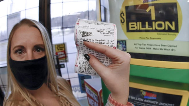 A patron, who did not want to give her name, shows the ticket she had just bought for the Mega Millions lottery drawing at the lottery ticket vending kiosk in a Smoker Friendly store, Friday, Jan. 22, 2021, in Cranberry Township, Pa. The jackpot for the Mega Millions lottery game has grown to $1 billion ahead of Friday night's drawing after more than four months without a winner.
