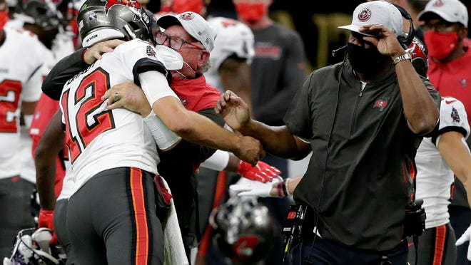 Tampa Bay quarterback Tom Brady hugs head coach Bruce Arians during the second half of the playoff game against New Orleans on Sunday night. The Bucs won 30-20.