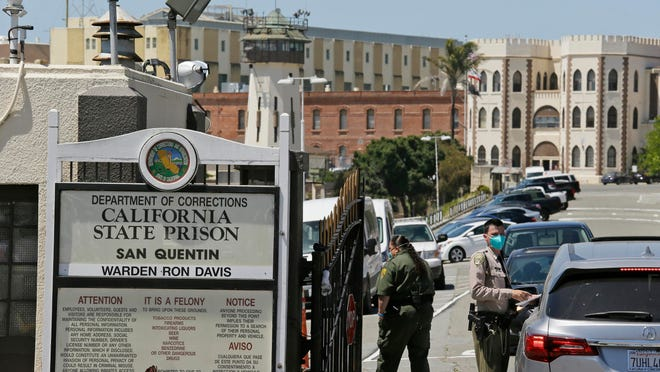 A correctional officer checks a car entering the main gate of San Quentin State Prison on July 9 in San Quentin, Calif.
