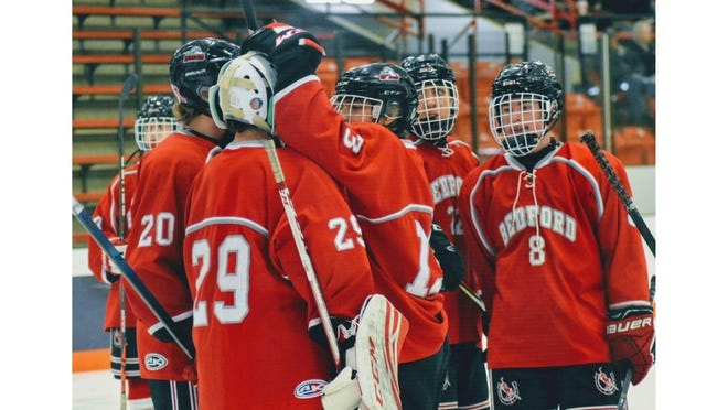 Bedford hockey players congratulate Mules' goalkeeper Zachary Ingalls (29) after a game last year.