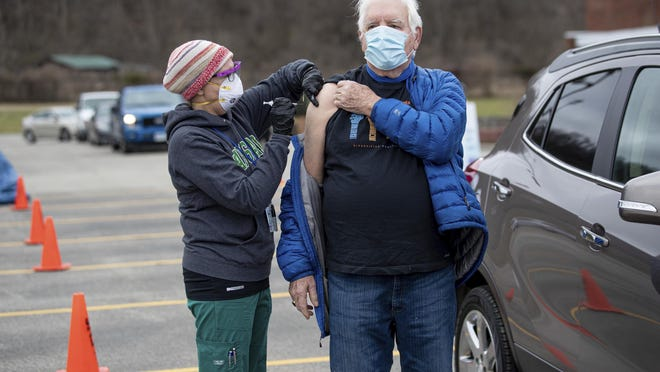 Joe Beasley, of Barboursville, receives a COVID-19 vaccine from Marshall University student nurse Angie Bush as health care workers with the Cabell County EMS and Cabell-Huntington Health Department administer vaccines during a drive-thru clinic Jan. 21 outside the St. Mary's School of Nursing in Huntington, W.Va.
