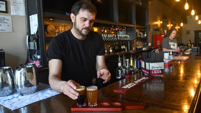 Stephen DeLucia prepares a beer flight at the Little Brown Barrel in downtown Minersville, Pa., on Monday.