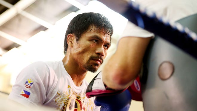 Manny Pacquiao works the mitts with trainer Freddie Roach during a workout session at The Venetian on Thursday in Macau, Macau.