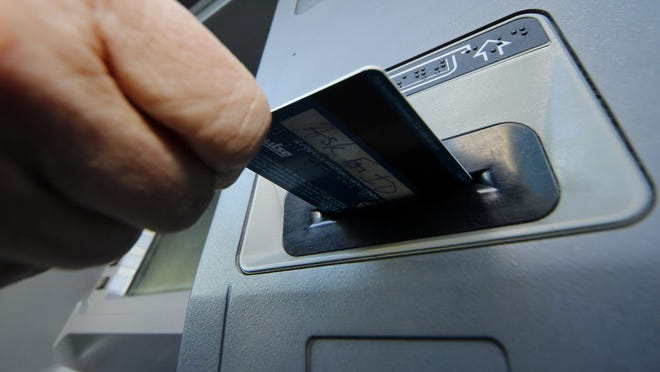 A person inserts a debit card into an ATM machine in Pittsburgh.