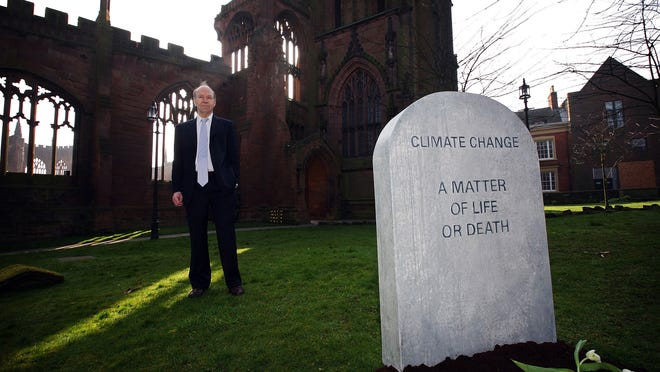 "World-famous climate scientist James Hansen walks next to a mock tombstone declaring ""Climate change, a matter of life or death."" He is shown outside the ruins of Coventry Cathedral in England in 2009, where he was appearing at a climate change action day."