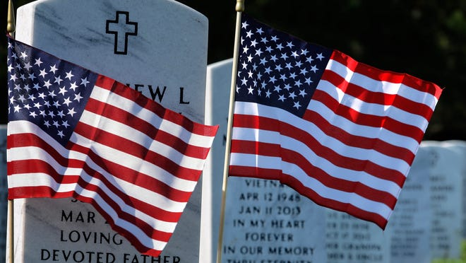 American flags decorate the graves on Monday at Camp Butler National Cemetery in Springfield, Ill., in preparation for Veterans Day.