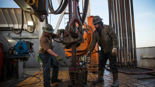 Workers with Raven Drilling line up pipe while drilling for oil in the Bakken shale formation outside Watford City, N.D., in July 2013.
