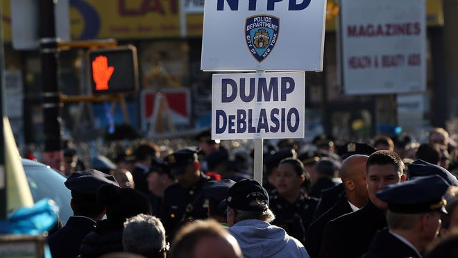 An anti-Mayor Bill de Blasio protester holds up a sign today outside of Christ Tabernacle Church for the funeral of slain New York City Police Officer Rafael Ramos, one of two officers murdered while sitting in their patrol car in an ambush in Brooklyn last Saturday afternoon.