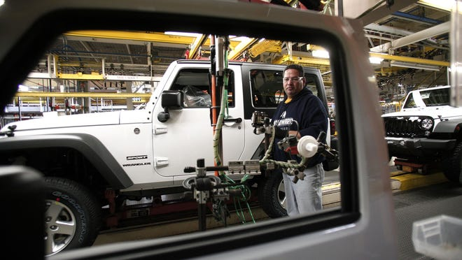 A worker installs doors on a 2014 Jeep Wrangler as it undergoes assembly at the Chrysler Toledo North Assembly Plant Jeep in May in Toledo.