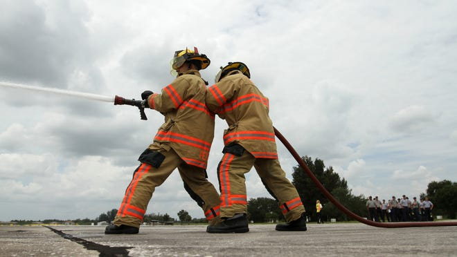 Jorge Perez and Taylor Cohen train with the Lehigh Acres Fire Department on Monday, August 16, 2010, in Lehigh Acres. The department was training 20 new recruits. The Lehigh Acres Fire Department is also helping with a benefit for Fort Myers Shores assistant chief Pete Gee to help pay for medical expenses. The benefit will be a fire fighter auction on Saturday, August 21, 2010, at the Big Game Bar and Grill on Fort Myers Beach at 6:30 p.m. Tickets are $25.