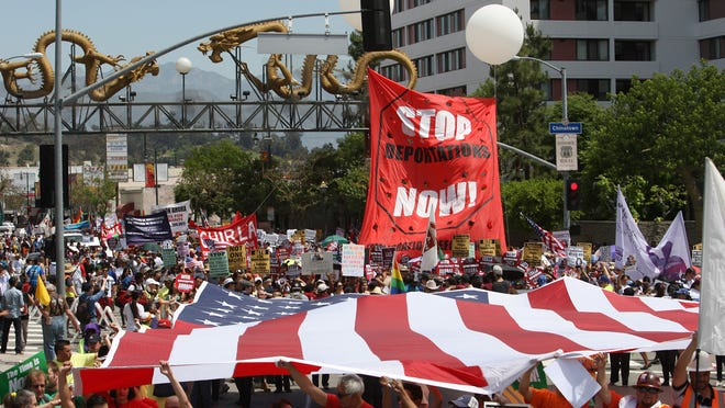 Marchers carry a huge American flag near the Chinatown Gateway as they march to the Metropolitan Detention Center during one of several May Day immigration-themed events in Los Angeles, California. Demonstrators are calling for immigration reform and an end to deportations of undocumented residents.