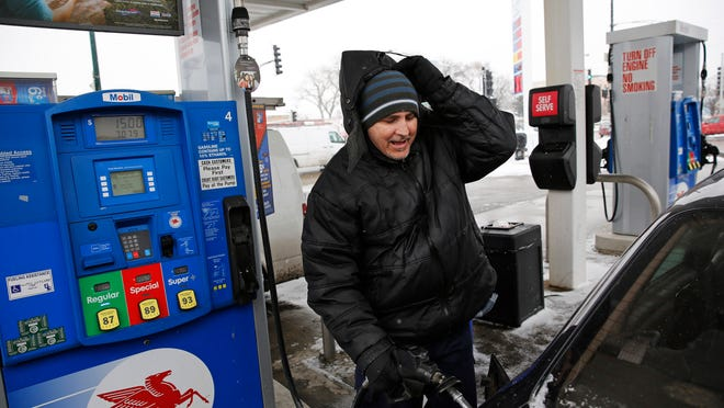 Manuel Casielles pumps regular gas at the Mobil gas station at the intersection of North Harlem and West Belmont avenues on Tuesday in Chicago.