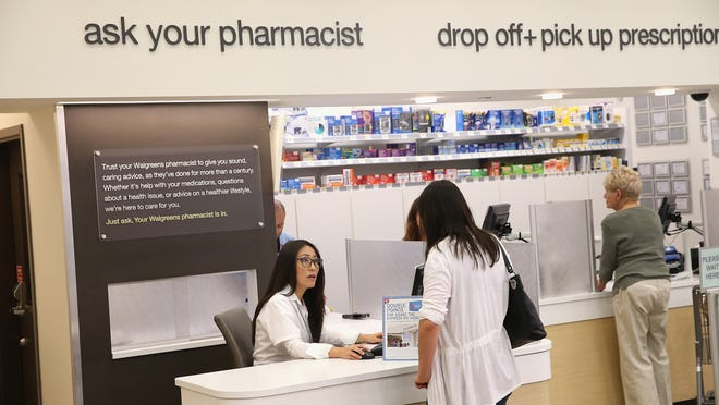 A pharmacist consults with a customer at a Walgreens in Wheeling, Ill. In 2011, the pharmacy chain proposed a plan to move pharmacists out from behind the counter to a workstation on the floor, where they could answer questions from the public and provide health counseling. Indiana was the pilot site.