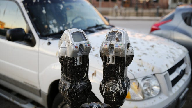 Crow droppings cover a parking meter near the Monroe County Courthouse in Bloomington. The birds have been wreaking havoc on the square since they've settled into the trees and dropped feces like raindrops on the pavement and cars below.