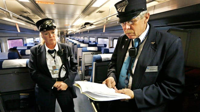 Assistant conductor Pam Fogarty looks on as conductor J.R. Richardson looks over a schedule of arrival times in November as Amtrak's Hoosier State train approaches Monon.