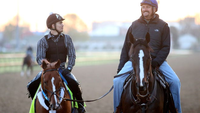 Trainer of Tapiture Steve Asmussen, right,  is seen riding next to Tapiture after a workout at Churchill Downs. April 26, 2014