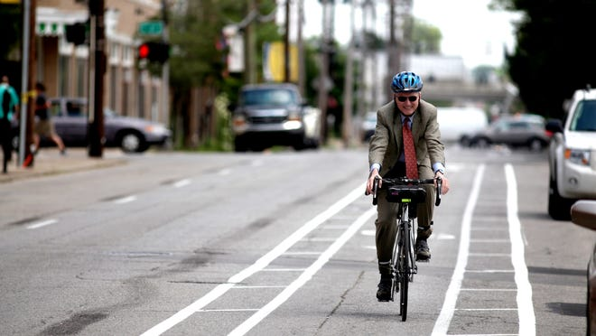 Louisville Free Public Library Director Craig Buthod rides his bike in the new bike lane on Breckinridge street on June 6.