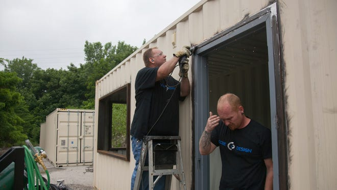 Kyle Gilman, left, with Core Design polishes the welding on a doorway of a kitchen as Jeremy Semones, owner of Core Design, passes through. July 1, 2014