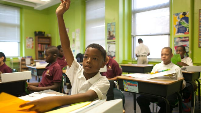 Antay Usher, age 11, raises his hand on the first day of class while organizing his school supplies donated by the school at Nativity Academy at Saint Boniface. Aug., 20, 2014