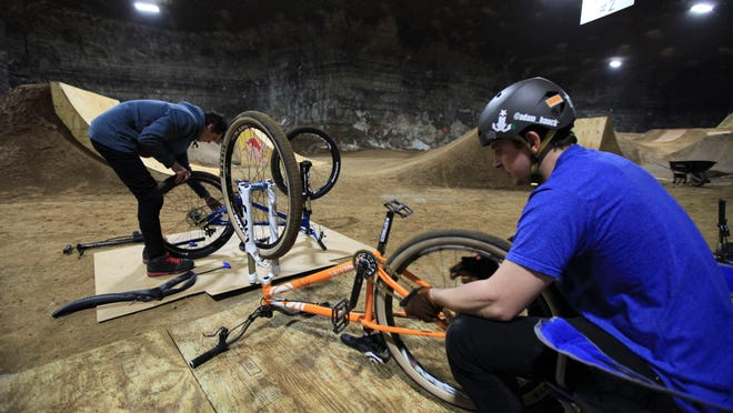Reed Boggs, left, and Adam Hauck get their bikes back into shape after warm up jumps at the Mega Cavern Bike Course. Boggs and Hauck.
