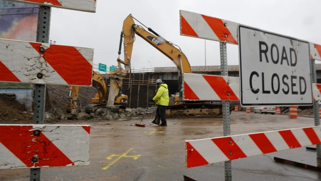 Enrique Machin Urgelles swept mud off of Main street as the old Interstate 65 overpass was being torn down. The continued drop in gasoline prices may imperil the state's road fund and future construction progress.