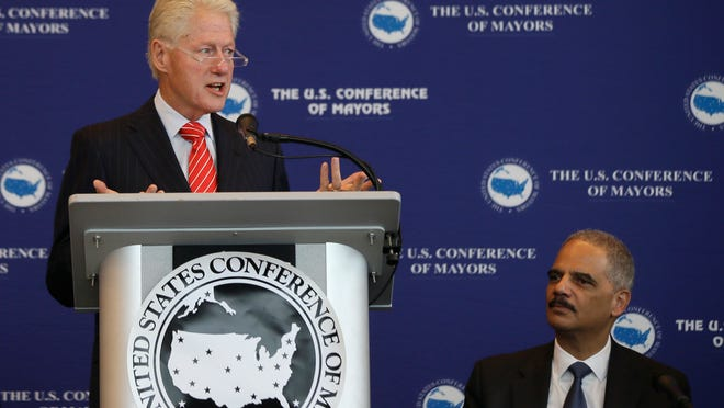 Former President Bill Clinton (left) speaks to a meeting of the U.S. Conference of Mayors at the Clinton Presidential Library in Little Rock, as U.S. Attorney General Eric Holder  listens on Wednesday.