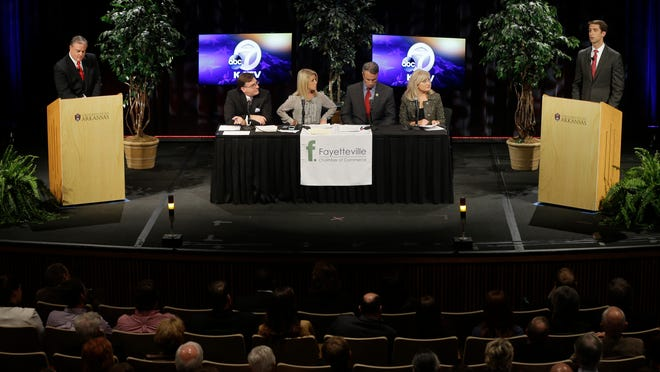U.S. Rep. Tom Cotton, R-Ark. (far right) speaks during a Senate debate as U.S. Sen. Mark Pryor, D-Ark., (far left) takes notes during a televised debate at the University of Arkansas in Fayetteville, Tuesday. Cotton is challenging incumbent Pryor in the November election.