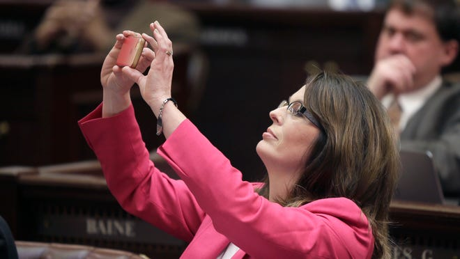 Rep. Julie Mayberry, R-Hensley, takes a picture using her cell phone as the vote is counted on a Senate bill she presented in the House chamber at the state Capitol in Little Rock, Ark., Thursday.