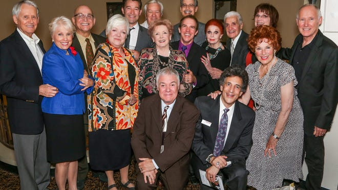The cast joins co-producers Michael Shaw (center, standing) and Clark Dugger (far right)
