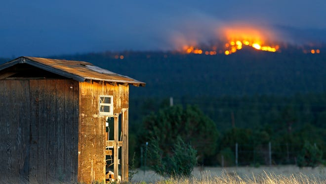 The San Juan Fire burns in far hills in this June 28 photo from Vernon.