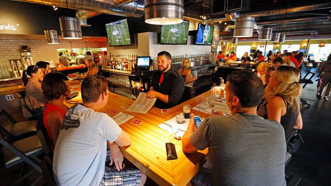 "Bartender Nick Westby helps customers at the Union Barrelhouse Saturday, Aug. 23, 2014 in Scottsdale, Ariz. The area is south of Indian School, north of Goldwater, and west of Scottsdale Road nicknamed ""SoDo,"" for south"