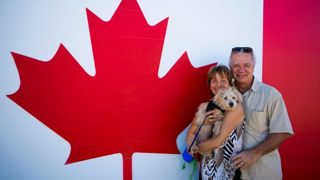 Rose and Tony Fabbro, originally from British Columbia, pose in front of the Canadian flag during the picnic. About 22,000 Maricopa County homes are owned by Canadians.
