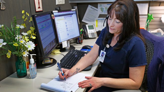 Jennifer Robinson, a registered nurse who formerly worked in an emergency room, is now a triage nurse in a Banner Health call center, helping direct callers to the appropriate care.