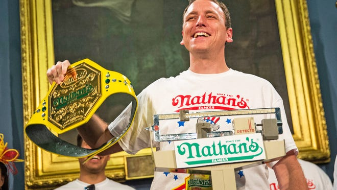 """Joey """"Jaws"""" Chestnut is officially weighed in the day before the Nathan's Hot Dog Eating Contest at City Hall in New York City on Thursday. Chestnut won the men's division contest Friday by eating 61 hot dogs."""