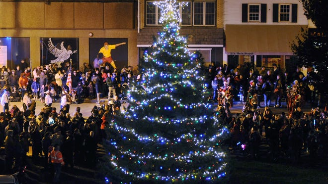 Holiday revelers gather near a Christmas tree on Main Street in the City of Poughkeepsie during the Celebration of Lights.