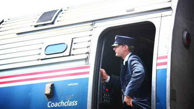 An Amtrak employee takes a peek at the track ahead as a train leaves Rochester's passenger station. Amtrak shut down its service between Albany and Buffalo Tuesday because of the intense lake effect snow that hit parts of the Buffalo area. It announced Thursday morning that it has resumed limited service.