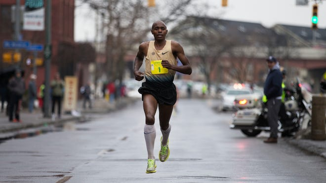 Kiplangat Tisia of Rochester finishes Johnny's Runnin' of the Green five-mile race in first on Exchange Blvd. on Saturday.