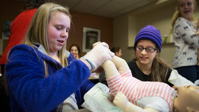 Cameron Taylor, 11, and Daisy Smania, 11, both of Henrietta change a fake baby's diaper during a babysitting course at the Prince St. Red Cross location on April 1, 2015.