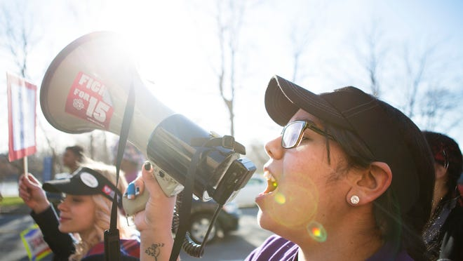 Alexsandra Candelaria yells into a megaphone as she leads marchers during a rally for a minimum wage of $15 on Wednesday. Candelaria is on a labor strike from her job at McDonald's on Jay Scutti Boulevard in Henrietta.