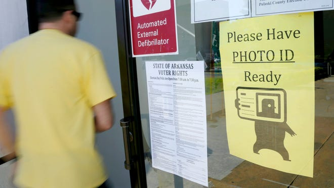 """A voter walks past a """"Please Have Photo ID Ready"""" sign as he enters an early-voting polling place on May 25 in downtown Little Rock, Ark."""