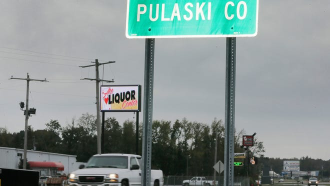"""In this Oct. 23, 2014 photo, traffic passes by a liquor store just inside the Pulaski County line near Cabot, Ark., which is in Lonoke County where alcohol sales are prohibited. The decision of whether a community has liquor stores has long been a local issue, with a patchwork of wet, dry and """"damp"""" counties spread across Arkansas. But a proposed constitutional amendment on the November ballot would do away with that tradition, instantly legalizing alcohol sales in all 75 counties if approved. (AP Photo/Danny Johnston)"""