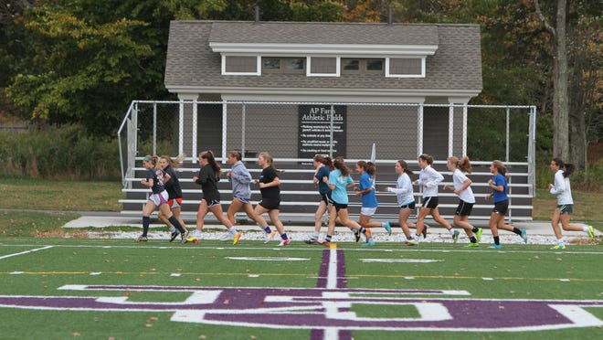 Members of the John Jay High School varsity girls soccer team warm up prior to taking practice on the AP Farm athletic fields at the school in Cross River Oct. 9, 2014.