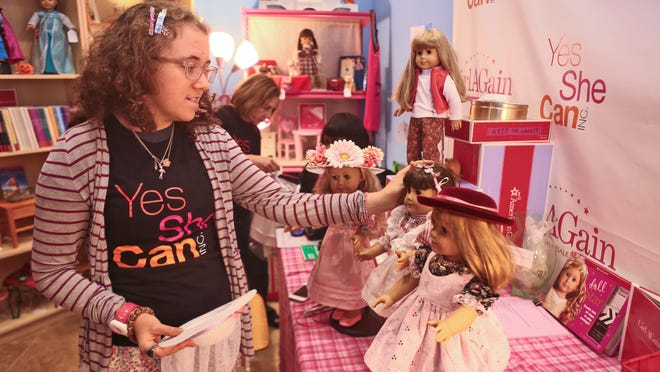 Isabelle Madfis adjusts the American Girl products on display at Girl AGain, a boutique that resells American Girl products. Girl AGain was created by Marjorie Madfis, Isabelle's mother, who started the not-for-profit corporation Yes We Can to help young women with autism develop job skills.