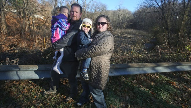 Erik Lindberg and Courtney Williams of Peekskill stand with their children Irene, 4, and Gunnar, 2, in front of the Algonquin pipeline right of way, which is within several hundred feet of their home Dec. 7, 2014. The couple, along with others in the neighborhood, are opposed to Algonquin's plan to expand their natural gas pipeline.
