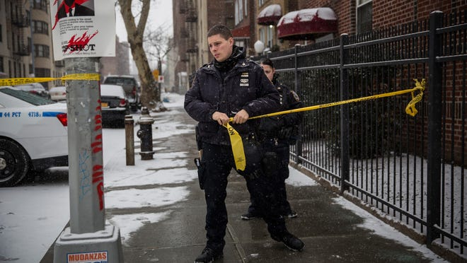 Police guard the perimeter of a crime scene Tuesday where two officers were shot and wounded Monday while responding to a robbery in the Bronx.