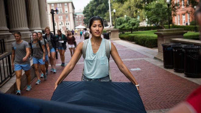 Columbia University student Emma Sulkowicz carries a mattress Sept. 5 in protest of the university's lack of action after she alleged being raped during her sophomore year. Sulkowicz has said she is committed to carrying the mattress everywhere she goes until the university expels the rapist or he leaves. The protest also is doubling as her senior thesis project.
