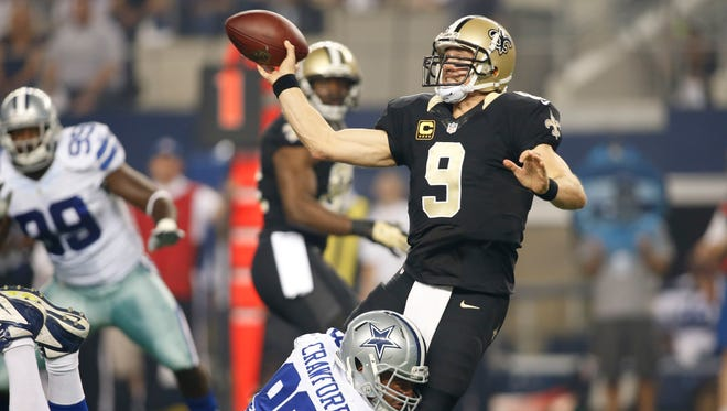 New Orleans Saints quarterback Drew Brees (9) throws a pass while being tackled by Dallas Cowboys defensive end Tyrone Crawford (98) in the second quarter at AT&T Stadium.