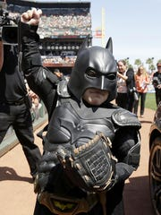 In this file photo from Tuesday, April 8, 2014, Miles Scott, dressed as Batkid, gestures after throwing the ceremonial first pitch before a baseball game between the San Francisco Giants and the Arizona Diamondbacks in San Francisco.