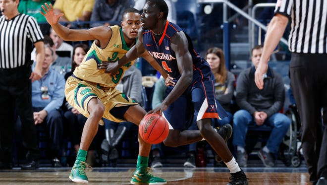 V.J. Beachem #3 of the Notre Dame Fighting Irish defends against Marial Shayok #4 of the Virginia Cavaliers in the first half of the game at Purcell Pavilion on January 10, 2015 in South Bend, Indiana.