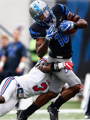 Tigers receiver Damonte Coxie (right) grabs a first-down catch against SMU defender Cedric Lancaster last season.